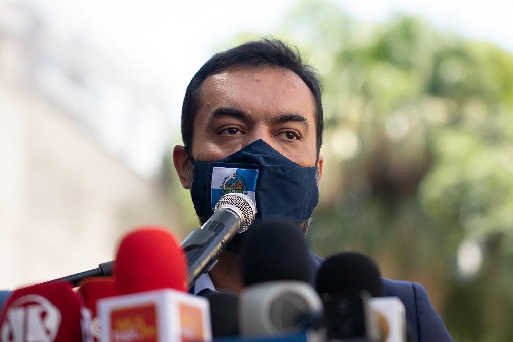 Cláudio Castro, governador do Rio, dá entrevista coletiva usando uma máscara escura