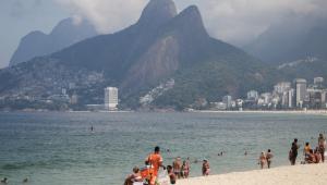 Pessoas caminhando na areia e montanhas ao fundo