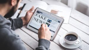 """Homem usa tablet em que está escrita a mensagem """"fake news"""""""