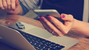 Mulher, cuja cara não aparece na imagem, usa o celular e o computador