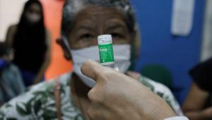 Enfermeira preparando dose da vacina da AstraZeneca para imunizar idosa em Manaus