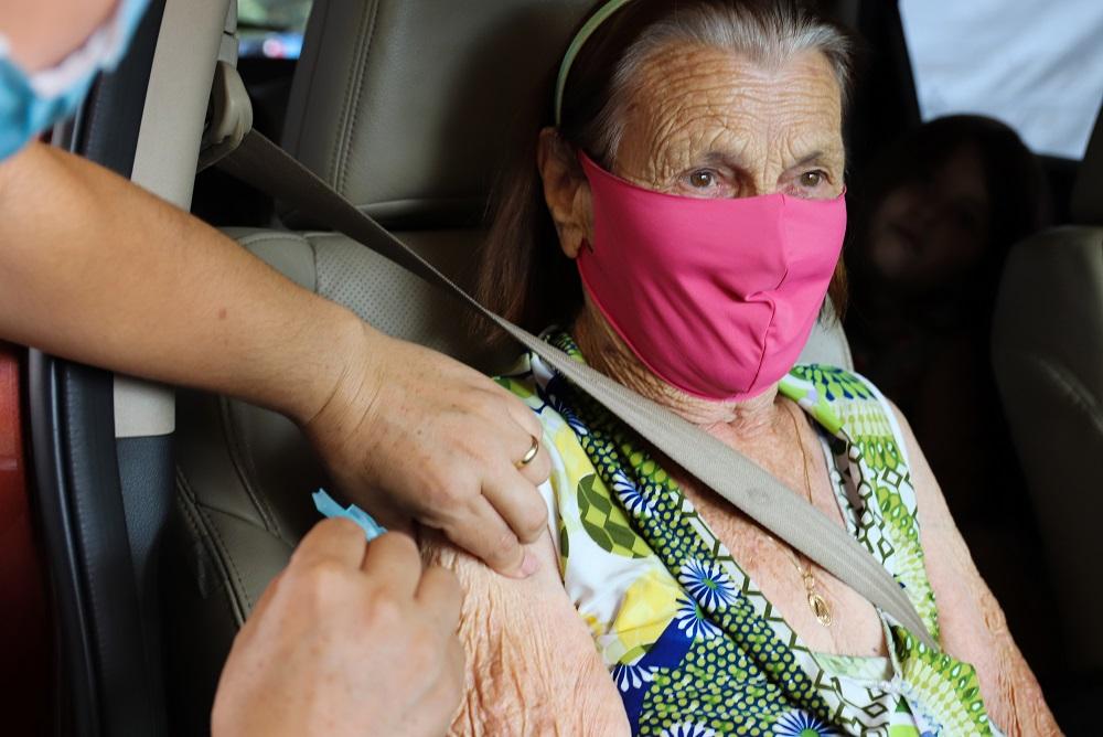 Dentro do carro, no banco do passageiro, idosa é vacinada em Foz do Iguaçu