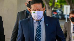 O vice-presidente JHamilton Mourão andando de máscara com um segurança atrás