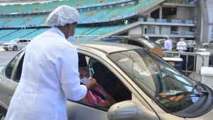 Enfermeira aplica vacina em uma idosa que está dentro de um carro parado no estádio da Fonte Nova