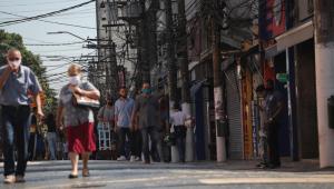 Pessoas andando na rua de máscara no bairro Santo Amaro, em São Paulo, enquanto as lojas estão fechadas