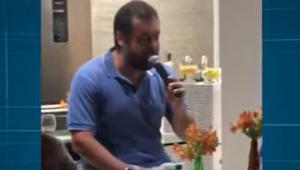 Homem de camisa azul falando em microfone