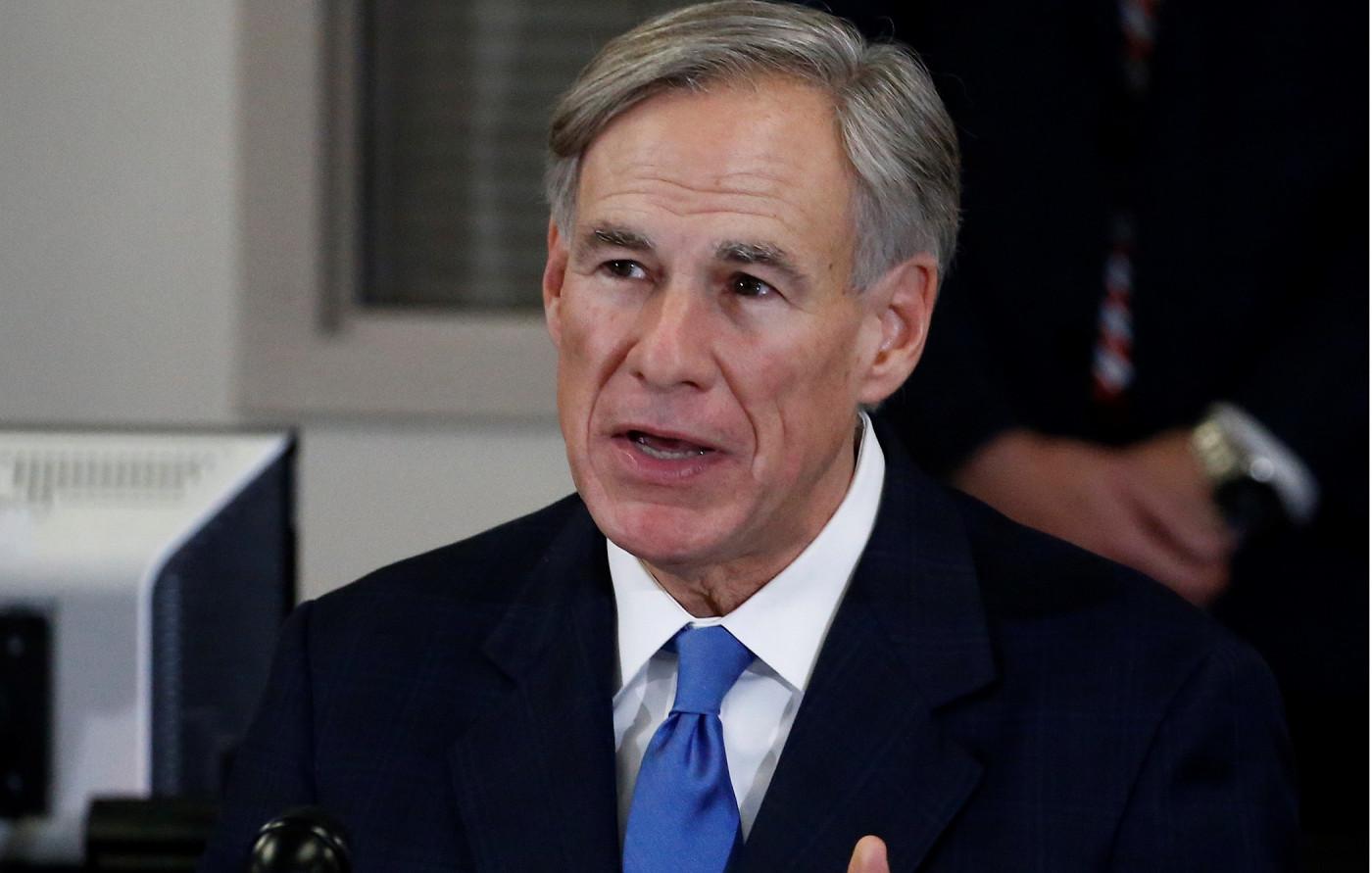 Homem de cabelo grisalho usando terno preto e gravata azul, é possível vê-lo da cintura para cima diante de um fundo desfocado da cor branca