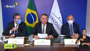 Três homens de terno e gravata sentados diante de mesa falando em microfones