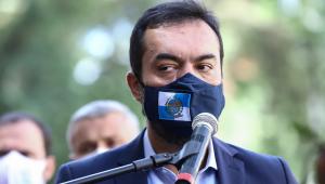 Claudio Castro de máscara falando em microfones durante coletiva de imprensa