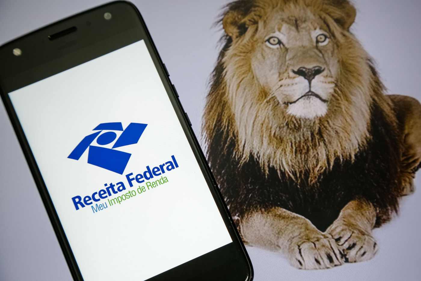 Símbolo da Receita Federal aparece em tela de celular, ao lado um leão