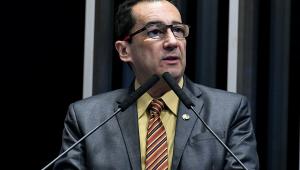 Senador Jorge Kajuru. Homem branco de óculos, terno azul e camisa amarela. Gravata listrada vermelha e azul escuro