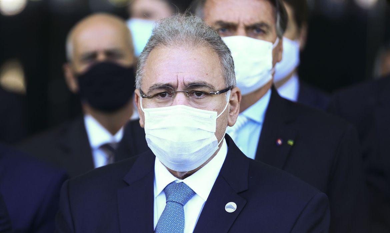 Homem de terno, máscara, gravata, óculos de armação preta e cabelos grisalhos