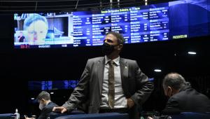 De terno e gravata, o senador Márcio Bittar aparece em primeiro plano com o placar do Senado ao fundo