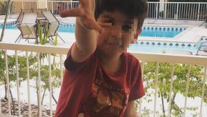 menino de camisa roxa estendendo mão com rosto borrado
