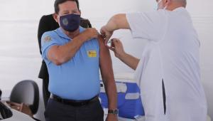 Homem de máscara e camisa azul sendo vacinado por enfermeiro careca, de máscara branca e trajes brancos