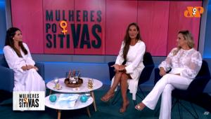 Três mulheres vestindo roupas brancas e sentadas em torno de uma mesa diante do nome 'mulheres positivas' em preto sobre tela rosa