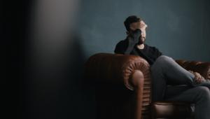 Homem sentado no sofá coloca a mão na testa e, desta forma, cobre o rosto