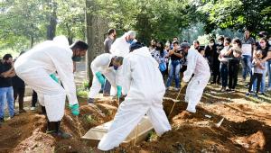 Vestidos com roupas de proteção, coveiros enterram vítima da Covid-19 na Vila Formosa