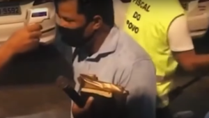 Homem mede a temperatura de um pastor antes dele realizar culto em um ônibus