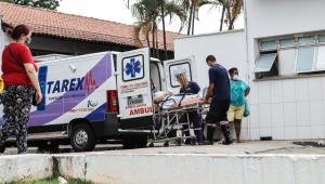 Três pessoas retiram maca de uma ambulância em frente ao hospital municipal Vereador Jose Storopolli, no bairro do Parque Novo Mundo, Zona Norte de São Paulo