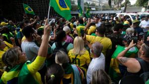 Pessoas usando camisa do Brasil e hasteando bandeira do Brasil durante aglomeração na rua