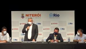 quatro homens sentados em uma mesa, com um painela atrás com os nomes 'Niterói' e 'Rio' escrito