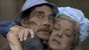 dona clotilde, mulher branca com touca branca na cabeça, abraça seu madruga, homem de chapéu e bigode. os rostos estão colados