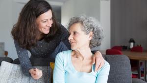 Sorrindo, filha adulta cuida da mãe idosa