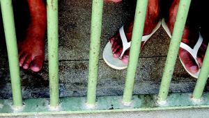pés de calçado atrás de grades