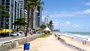 faixa de areia cercada de prédios diante do mar