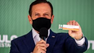 Homem olhando para frente com microfone e caixa na mão