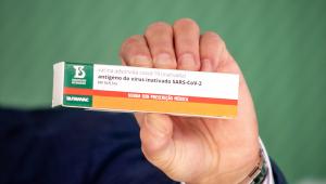 Caixa branca, laranja e verde sendo segurada por uma mão