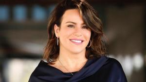 De vestido preto e brincos de argola, a jornalista Débora Aguillar aparece do pescoço para cima; ela tem a pele clara e os cabelos castanhos, na altura do pescoço