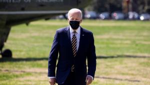 O presidente Joe Biden caminha em um gramado em Washington após descer do helicóptero, visto parcialmente ao fundo na imagem