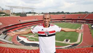 De braços abertos e vestindo a camisa do São Paulo, o zagueiro Miranda posa para foto na arquibancada do Morumbi