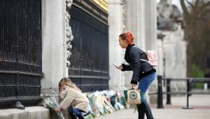 Mulher e criança deixando rosas diante do palácio de buckingham