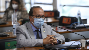 Homem com terno de cor clara e máscara sentado