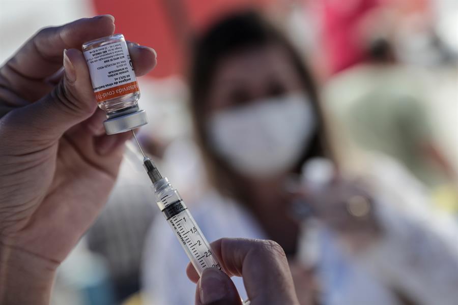 Pessoa passando o líquido da vacina CoronaVac para a seringa