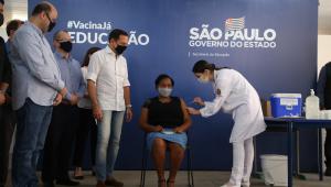 Merendeira Silmara sentada recebendo vacina de enfermeira