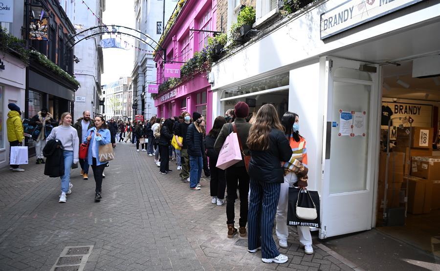 Pessoas fazem fila do lado de fora de lojas em Londres, que reabriram nesta segunda-feira, 12