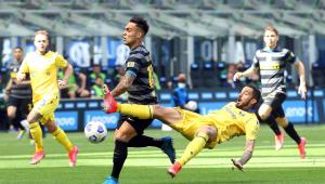 Jogador em queda após dar um chute na bola. Usa uniforme vermelho. Outro jogador aparece correndo ao lado em direção à bola, com uniforme listrado preto e azul marinho