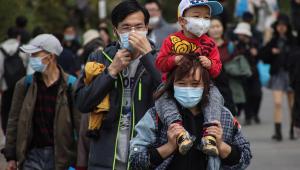 Mulher chinesa com uma criança no cangote, ambos de máscara, anda nas ruas de Pequim
