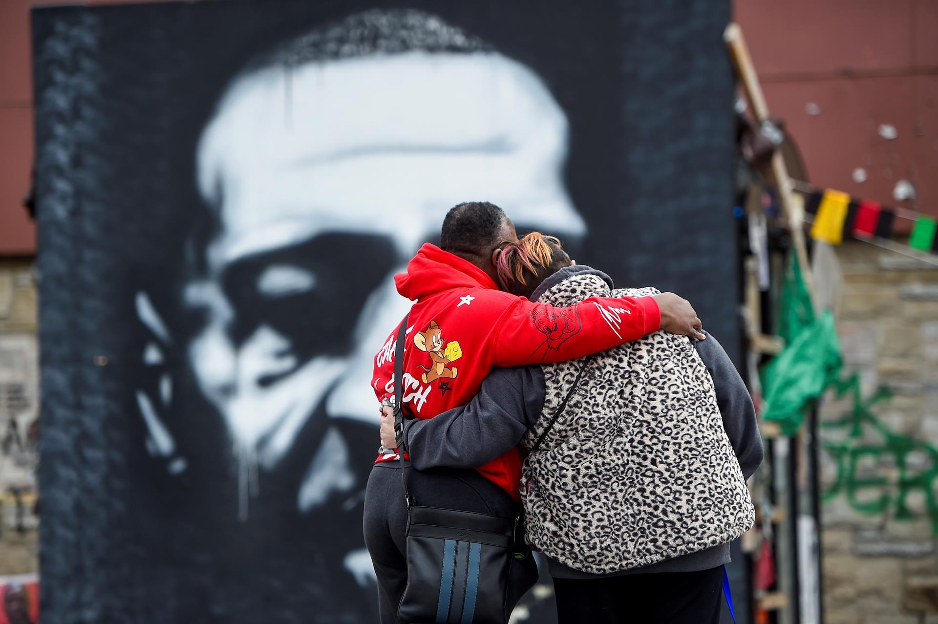 Casal observa mural que homenageia George Floyd