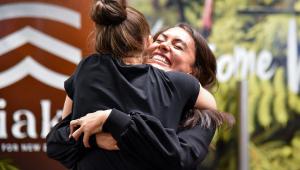 Duas mulheres sorrindo e se abraçando