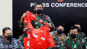 Oficias da Marinha da Indonésia seguram um colete salva-vidas