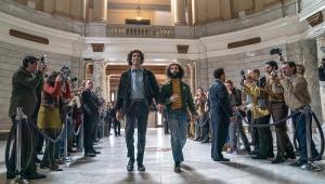"Sacha Baron Cohen e Jeremy Strong atravessam corredor durante cena do filme ""Os Sete de Chicago"""