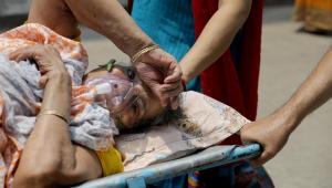Profissionais da saúde atendem paciente com suspeita de Covid-19 em Kolkata, na Índia