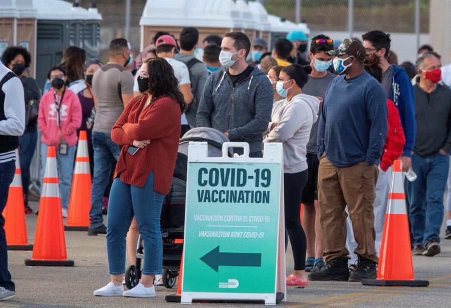 Pessoas esperando na fila para serem vacinadas nos Estados Unidos. Uma placa escrita 'Vacinação contra Covid-19' mostra a direção da fila