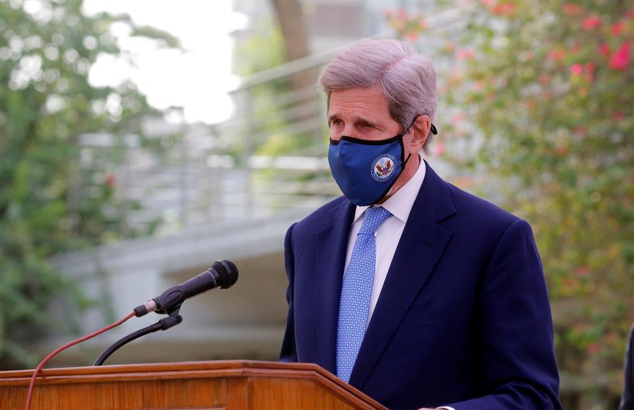 Homem de terno e máscara discursa em palanque
