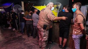 Frequentadores de uma festa clandestina em São Paulo são abordados por um funcionário da Vigilância Sanitária